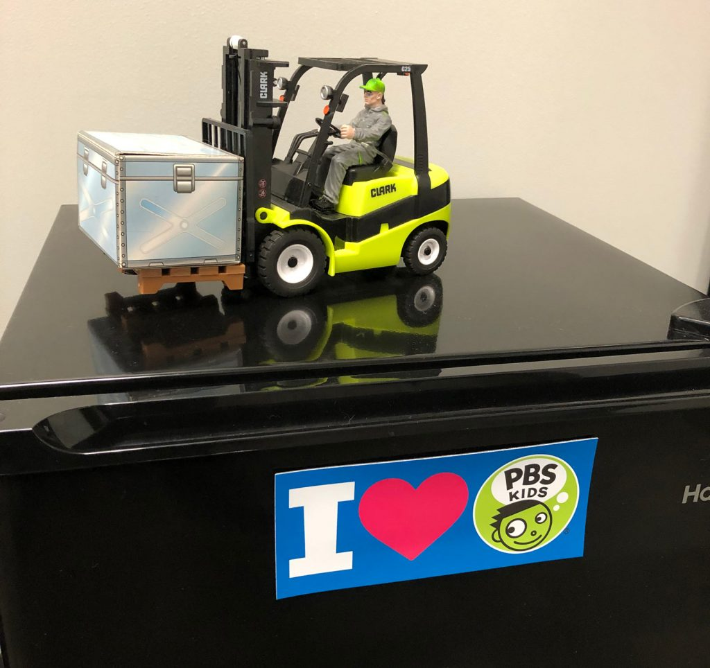 """A toy forklift on top of a mini fridge with an """"I heart PBS Kids"""" sticker on it."""