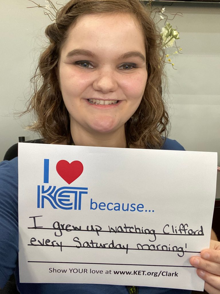 """Woman holding a sign that says """"I heart KET because I grew up watching Clifford every Saturday morning!"""""""