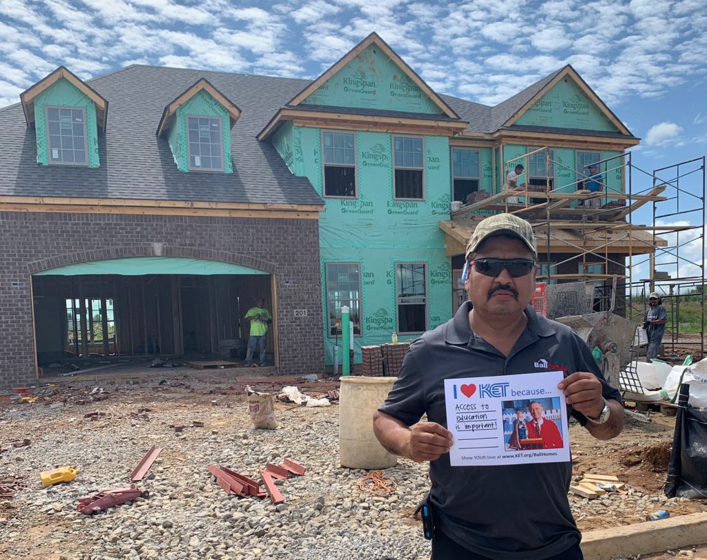 """Man standing in front of a house under construction holding a sign that says """"I heart KET because access to education is important!"""""""