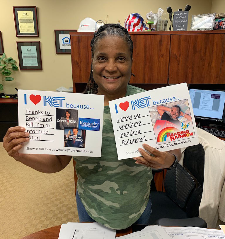 """Woman holding signs that say """"I heart KET because thanks to Renee and Bill, I'm an informed voter!"""" and """"I heart KET because I grew up watching Reading Rainbow!"""""""