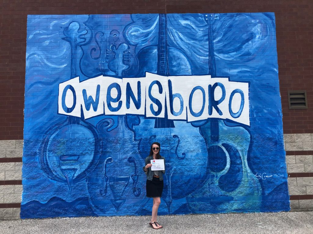 """Woman in front of a mural that says """"Owensboro"""" holding a sign that says """"I heart KET because they have the best TV shows!"""""""