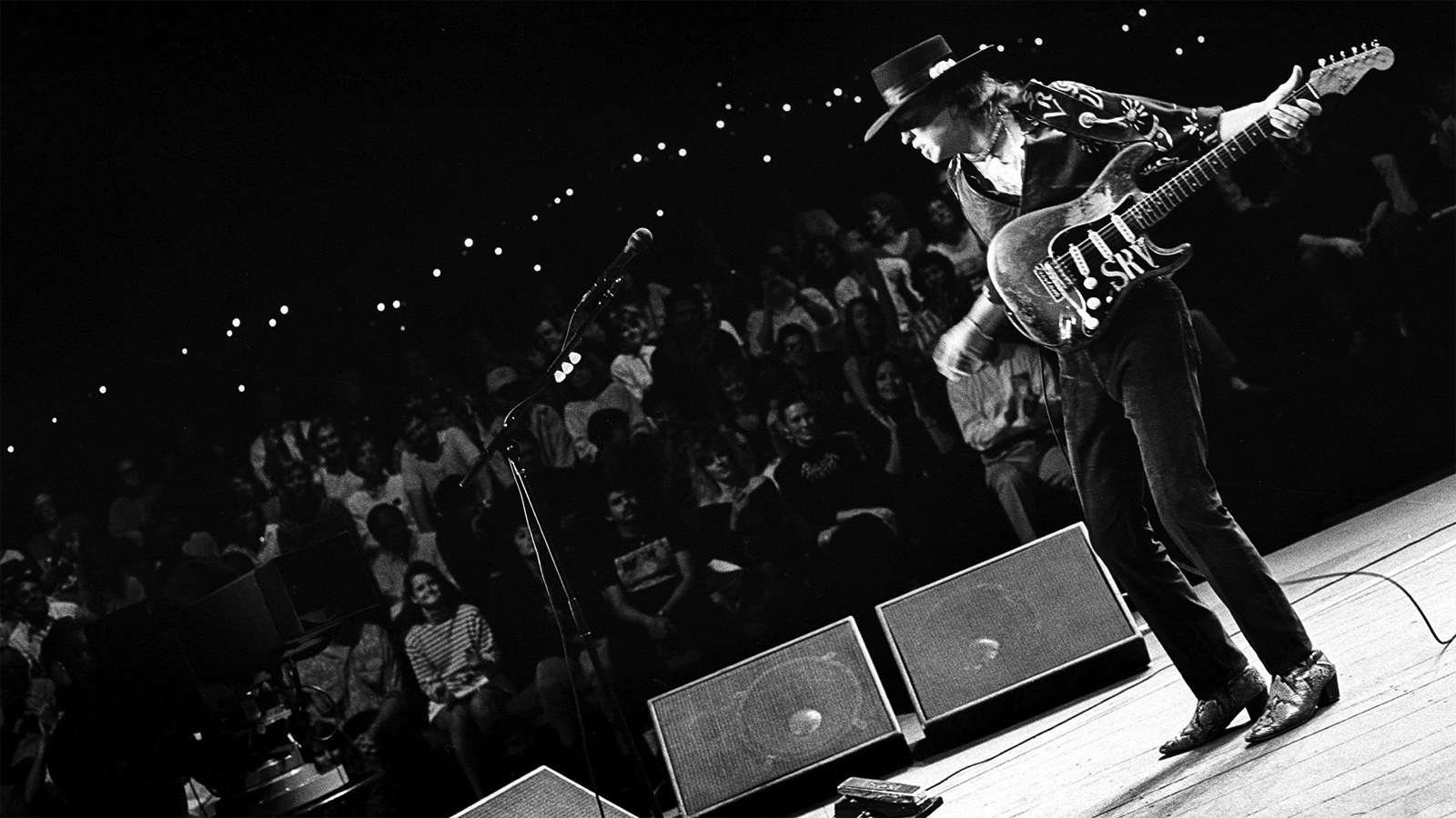 Black and white photo of Stevie Ray Vaughan playing guitar on the Austin City Limits stage