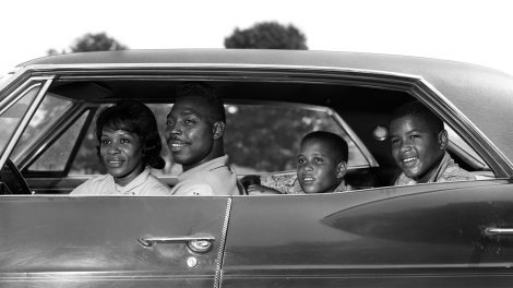 1960s photo of an African American family sitting in a sedan and smiling
