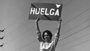 "Black and white photo of a woman holding up a sign that says ""HUELGA"""