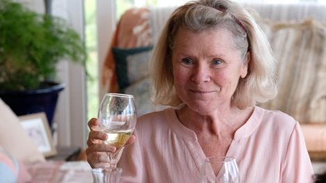Imelda Staunton as Mary smiling and holding a glass of white wine