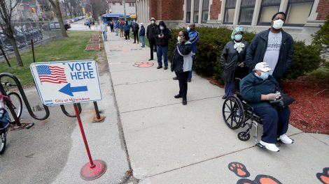 """A long line of voters wearing face masks and standing distanced from each other near a """"VOTE HERE - City of Milwaukee"""" sign"""