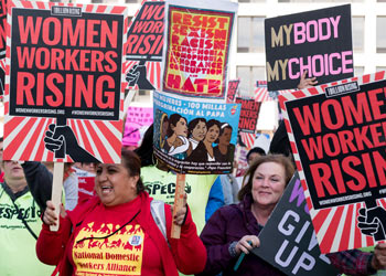 "Women attend a protest in support of workers rights, holding signs that say ""Women Workers Rising,"" ""Resist Sexim, Racism, Xenophobia, Corruption and Hate"" and ""My Body, My Choice."""
