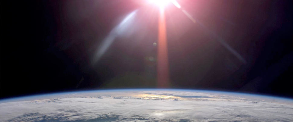 View from space of the edge of the earth with the sun in the background