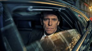 Hugh Laurie as Peter Laurence sitting in the backseat of a car with the window partially rolled down