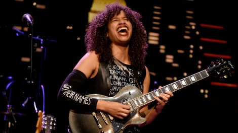 """Jackie Venson singing and playing guitar on stage. She is wearing a sleeve that says """"Say their names"""" and a dress with a list of names of Black victims of police violence."""