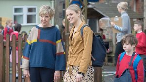 Julie Hesmondalgh as Jill Wheadon standing with Emily Reid as Roxanna Dubiki in front of a school yard smiling at something out of frame