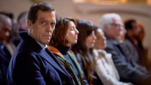 Hugh Laurie as Peter Laurence sitting at the end of a row of people in a crowd, looking off screen as everyone else looks straight ahead.