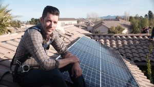"""Power Trip"" director Jonathan Scott posing on a rooftop next to recently installed solar panels"