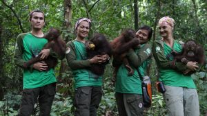 Dr. Signe Preuschoft (far right) and her team of local caregivers in Borneo are passionate about rehabilitating orphaned baby orangutans.