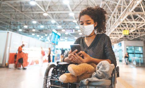 A young woman waits at an airport during the holiday season while wearing a mask.