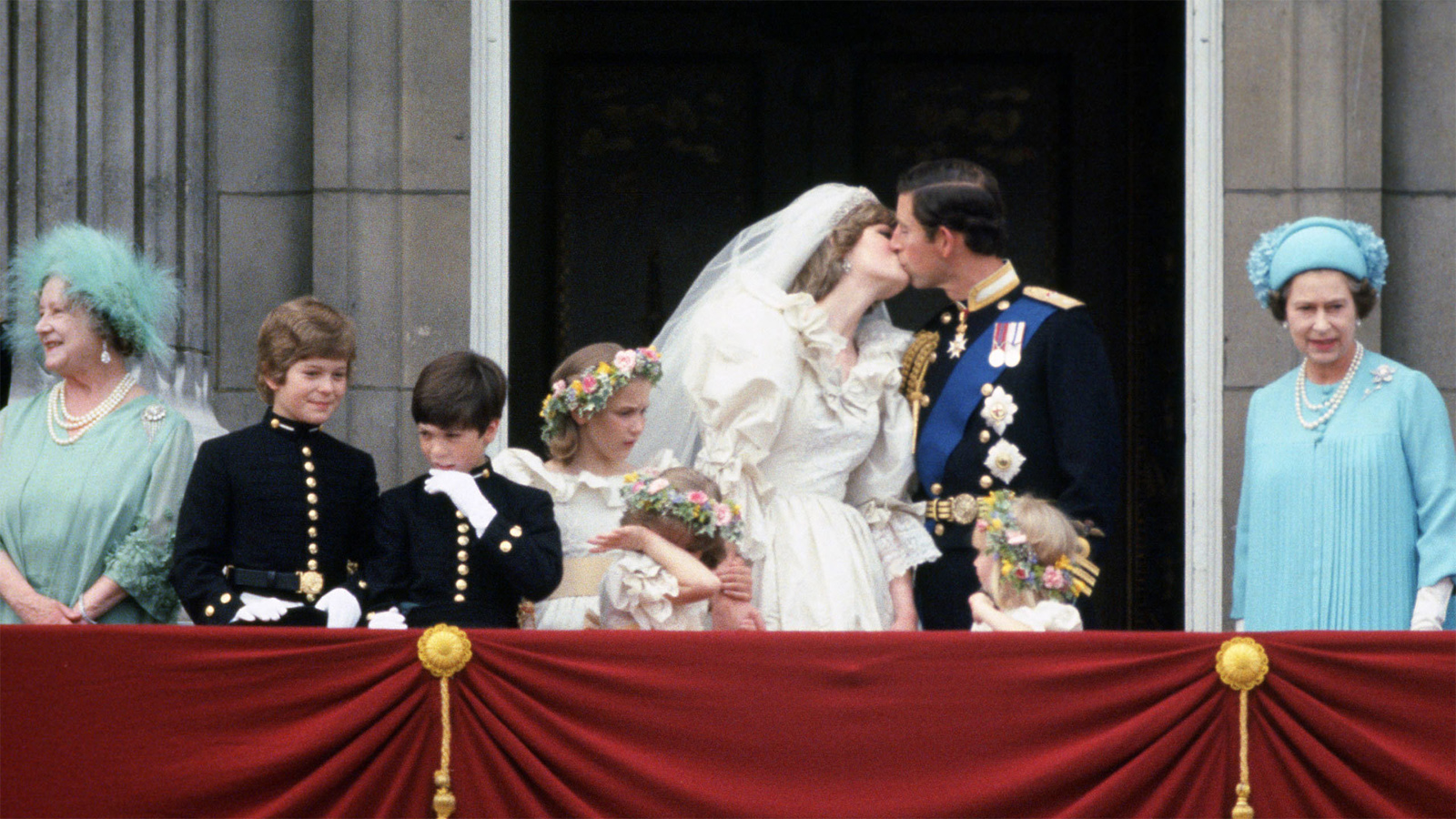 Prince Charles and Princess Diana kissing on the balcony on their wedding day, surrounded by members of the royal family.