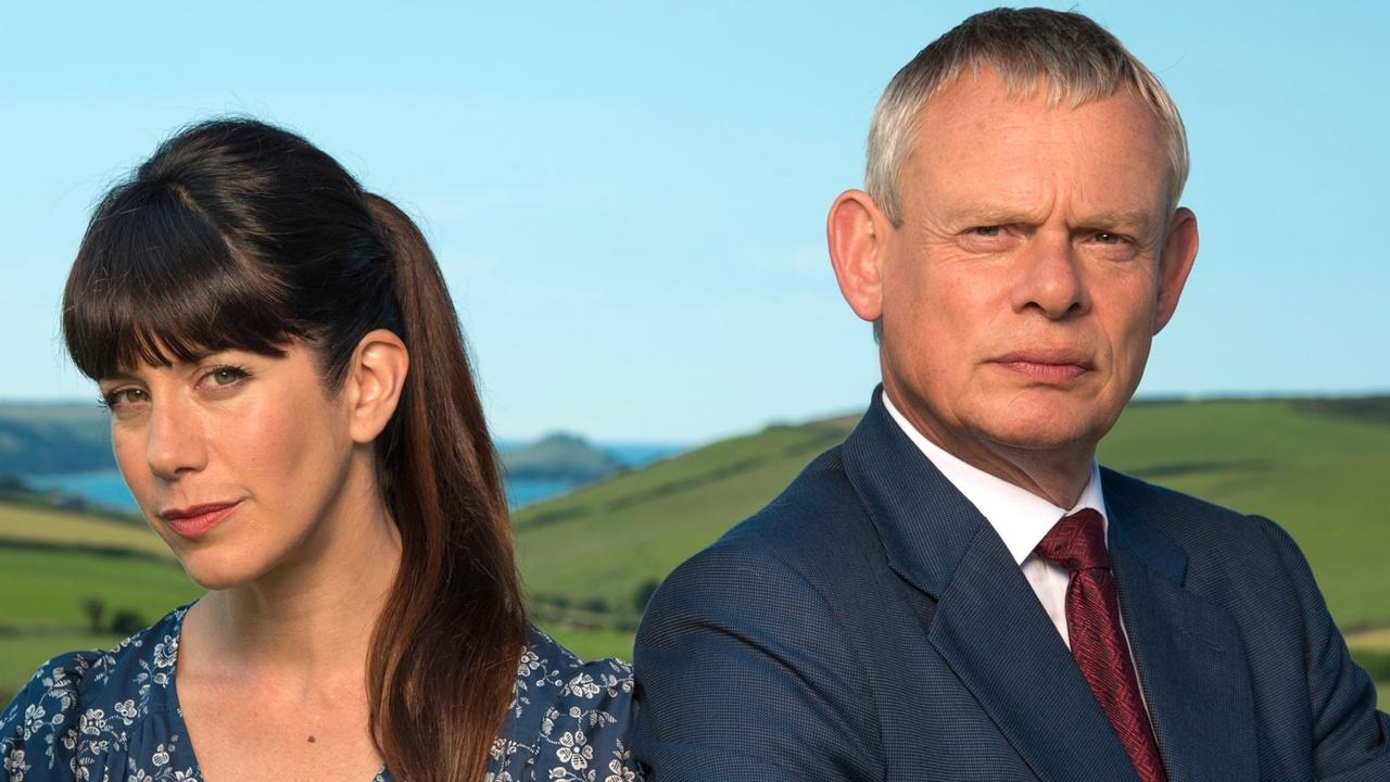 Doc Martin and Louisa posing with a background of green hills and blue sky.