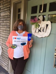 """A woman holding a sign that says """"I heart KET because ME LOVE COOKIES!"""" and a picture of Cookie Monster"""
