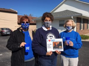 """Three women in facemasks standing outdoors holding a sign that says """"I heart KET because I'm like Lady Violet...I am never wrong"""""""