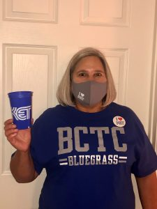 "Woman wearing a BCTC Bluegrass T-shirt with an ""I heart KET"" sticker, an ""I heart KET facemask"" and holding a KET cup."