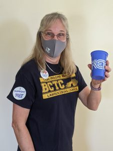 """A woman in a BCTC T-Shirt wearing stickers that say """"I heart KET"""" and """"I support KET,"""" holding a KET cup and wearing an """"I heart KET"""" facemask."""