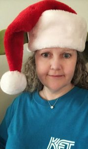 A woman in a KET T-shirt and a Santa hat
