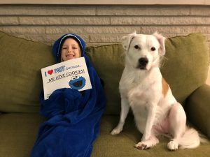 """A young girl in a snuggie holding a sign that says """"I heart KET because ME LOVE COOKIES"""" with a picture of Cookie Monster, and sitting on a green couch next to a white and tan dog"""