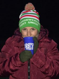 """A woman in wearing a winter coat and gloves and a winter hat that says """"Commonwealth Credit Union"""" on it, drinking out of a KET cup"""