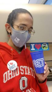 """A woman in an Ohio State sweatshirt with an """"I heart KET"""" button, holding a KET cup, wearing an """"I heart KET"""" mask, and with an """"I heart PBS Kids"""" sticker behind her."""