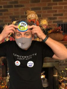 """A man in a Commonwealth Credit Union T-Shirt with an """"I heart KET"""" and an """"I Support KET"""" sticker and holding a """"PBS Kids"""" sticker to his forehead."""