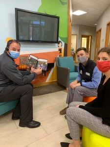 A man holding a childrens' book, sitting in a lounge area of an office building with a man and a woman, all wearing face masks.