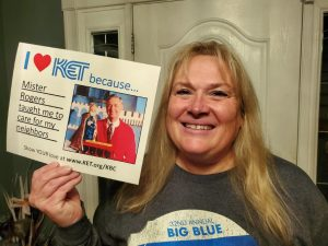 """Woman holding a sign that says """"I heart KET because Mister Rogers taught me to care for my neighbors"""""""