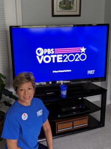 A woman in a KET t-shirt in front of a screen with the PBS Vote2020 logo on it