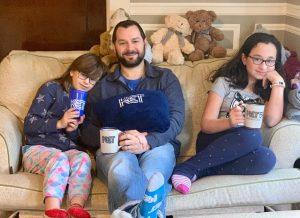 A father and two daughters sitting on a loveseat holding KET cups