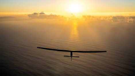 A solar powered aircraft viewed from above flying over a body of water toward the sun on the horizon.