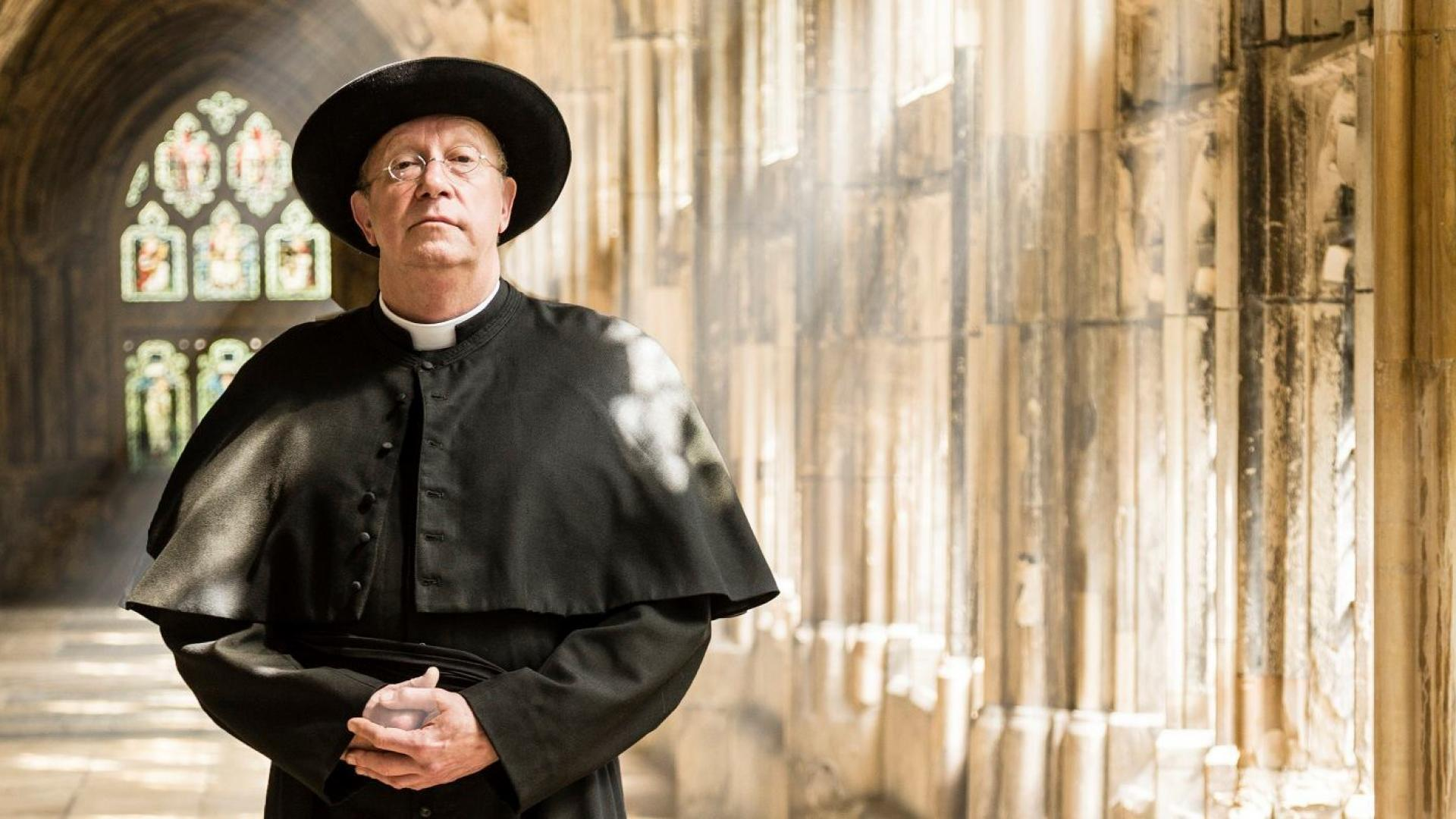 Father brown standing inside a church with bright sunlight coming through the windows