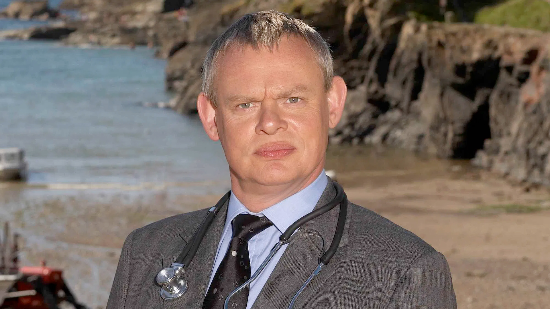 Martin Clunes as Doc Martin standing in front of a rocky coastline.