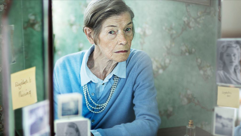Actor Glenda Jackson dressed as lead character Maud in a blouse with a light-blue cardigan and a pearl necklace looks into a mirror lined with photos and sticky notes.