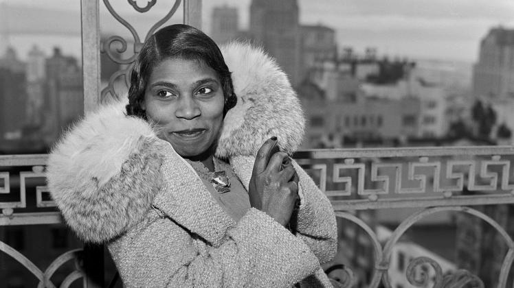 Marian Anderson in a coat with a large furry collar next to a railing with cityscape in the background.