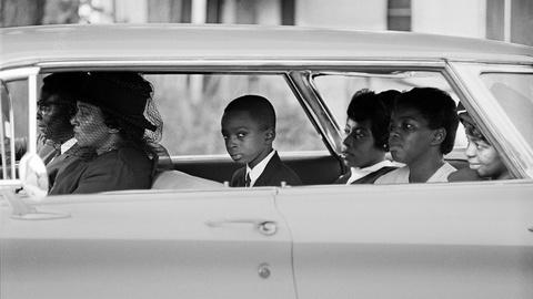 A black and white photo of a close-up of a car with several adults inside along with one boy who looks straight at the camera.