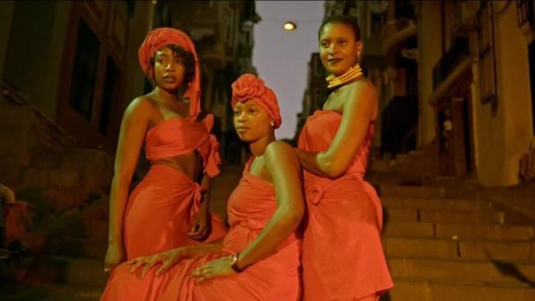 Three women in red tops, skirts, and dresses, and their heads wrapped in red fabric pose on steps outside between buildings.