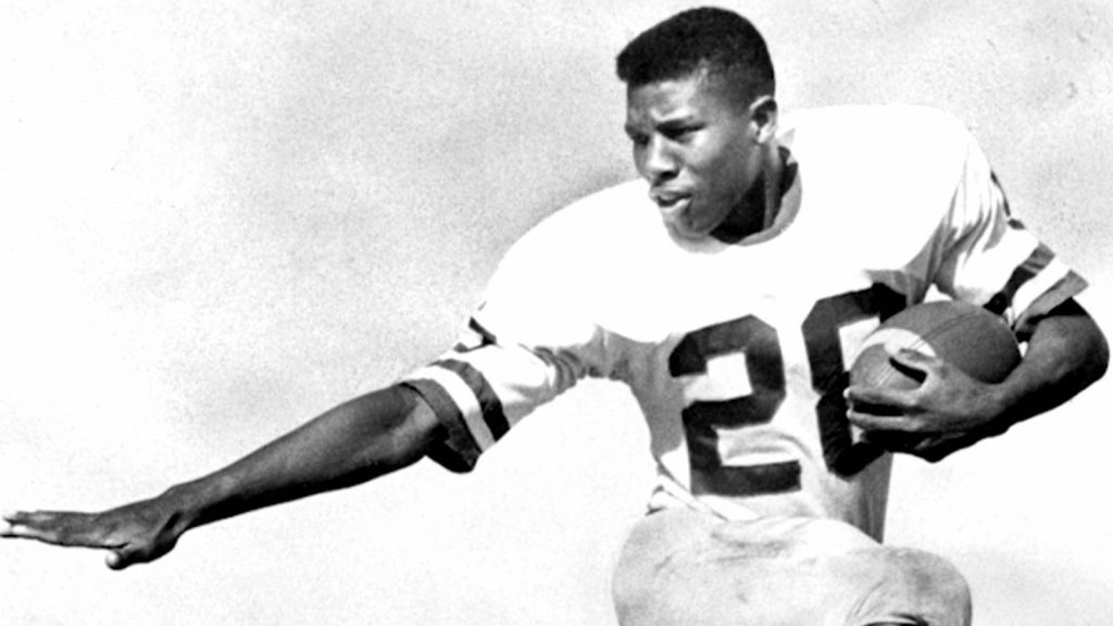 A black and white photo of a football player in a jersey with 20 on the chest holds a ball in his left arm and extends his right in a protective gesture.