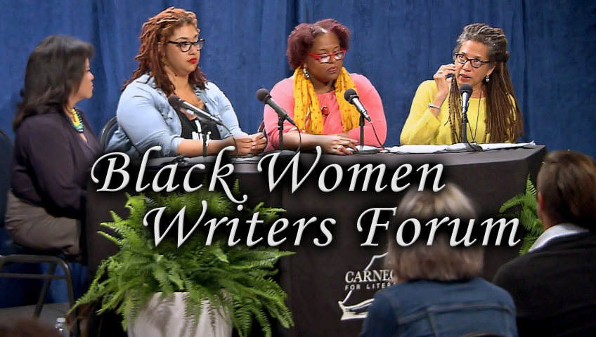 Renee Shaw, Bianca Lynne Spriggs, Crystal Wilkinson, and Nikky Finney sit at a table with microphones. In the foreground are a fern and two audience members and in the back is a blue curtain.