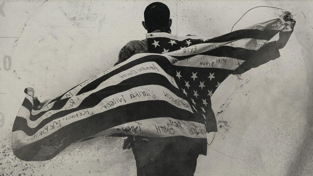A black and white photo of a man with his back to the camera with a US flag waving behind him. On the white lines on the flag, names are written.