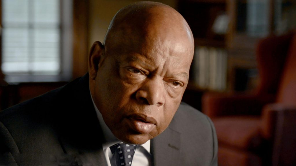 A close up of John Lewis in a coat and tie.