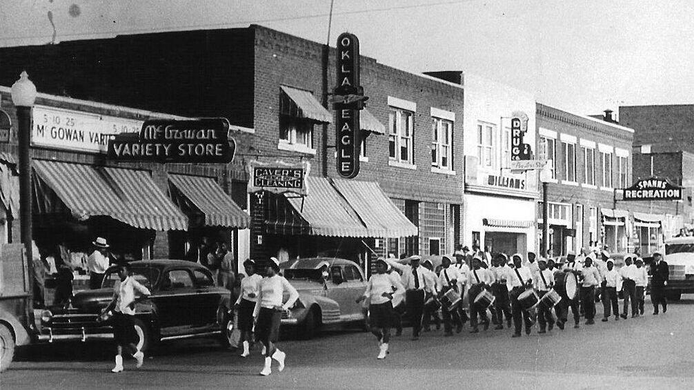 A black and white photo of Tulsa shop fronts with a marching band in the road.