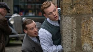Callum Woodhouse as Tristan Farnon and Nicholas Ralph as James Herriot looking surreptitiously around the corner of a building
