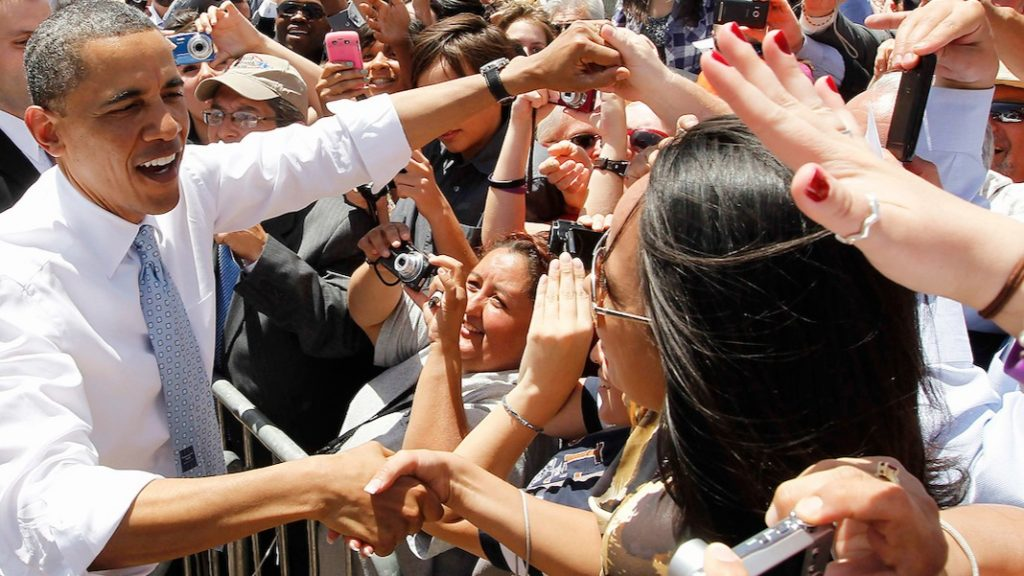 Barack Obama in a tie and white shirt with sleeves rolled up uses both hands to shake hands with people in a crowd behind a barricade.