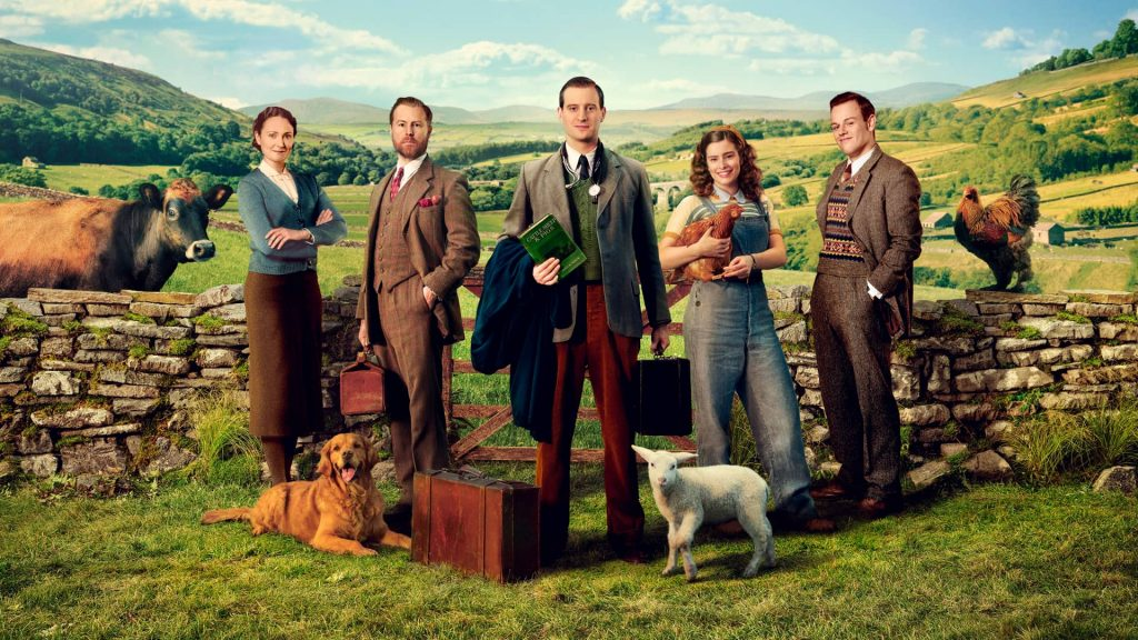 The cast poses in period costumes with a dog and lamb in front of a low stone wall with rolling hills and a sunny sky in the background.