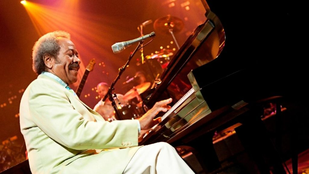 Allen Toussaint in a light-colored suit plays piano on the Austin City Limits stage.